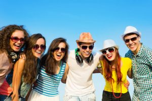 group of young adult friends huddled together and wearing sunglasses