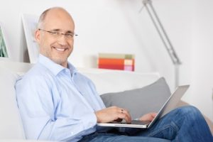 middle aged man using a laptop and smiling