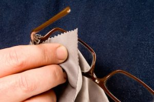 close up of someone cleaning glasses with a lens cloth