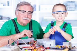 a man and his grandson tinkering with electronics while wearing safety goggles
